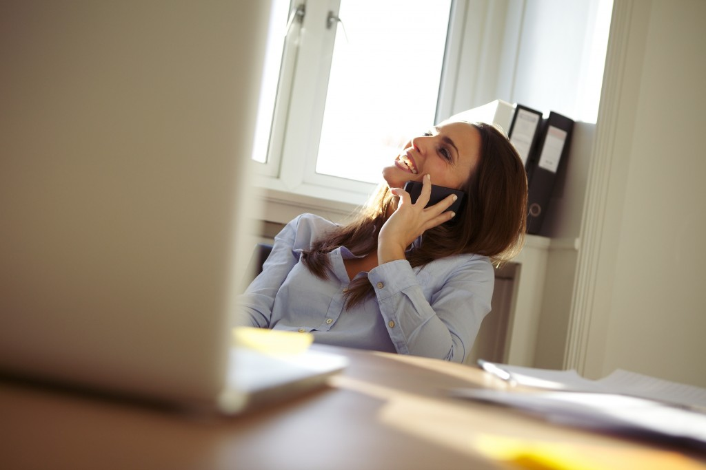 Beautiful young businesswoman sitting at her desk talking on mobile phone smiling. Pretty caucasian woman working in home office.