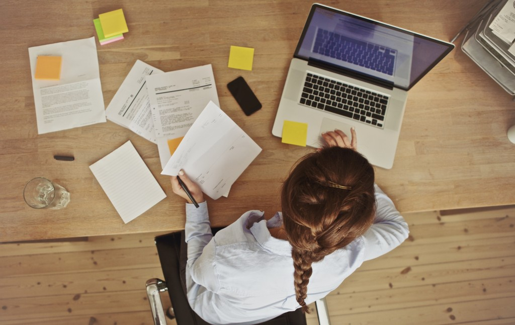 High angle view of an young brunette working at her office desk with documents and laptop. Businesswoman working on paperwork.